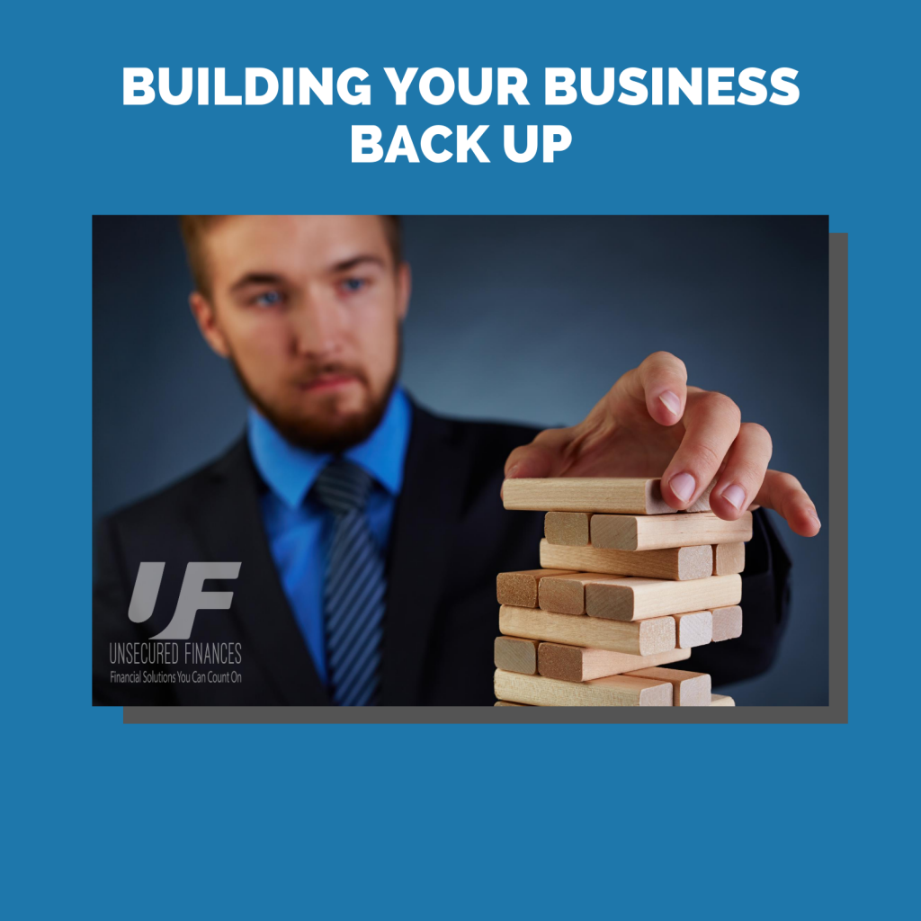 Business man using Jenga as building blocks to represent building the business back up